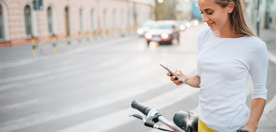 Frau am Fahrrad mit Smartphone
