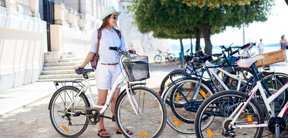 Touristin mit Rad an Fahrradständer