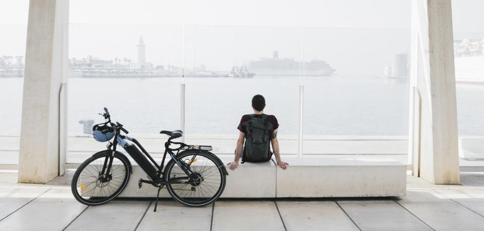 Mann mit abgestelltem E-Bike am Hafen
