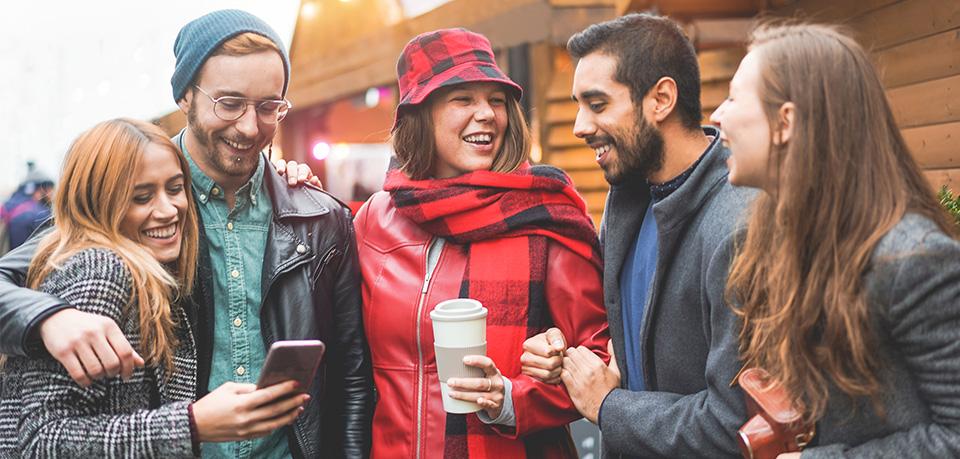 Gruppe auf Weihnachtsmarkt mit Smartphone
